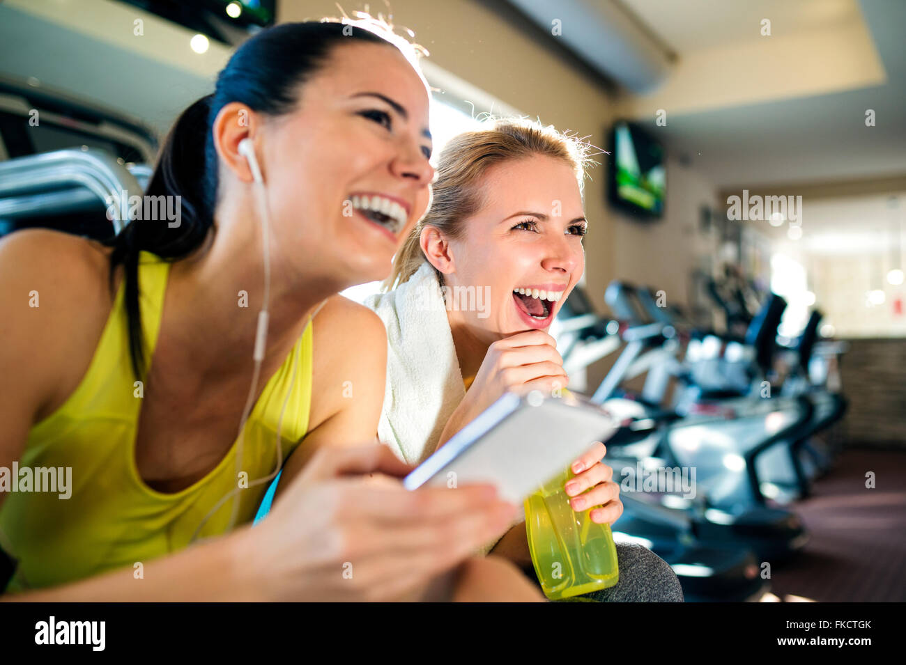 Attractive fit women in gym with smart phone laughing - Stock Image
