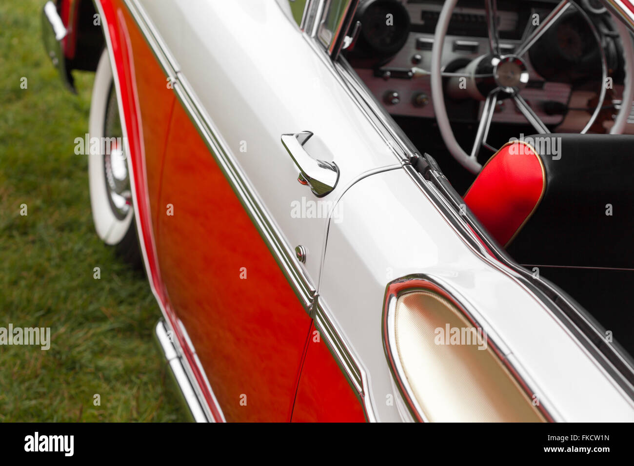 Car handle of a red and white classic convertible vintage car - Stock Image