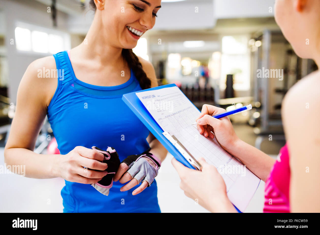 Woman in gym, personal trainer, consultiing plan on clipboard Stock Photo