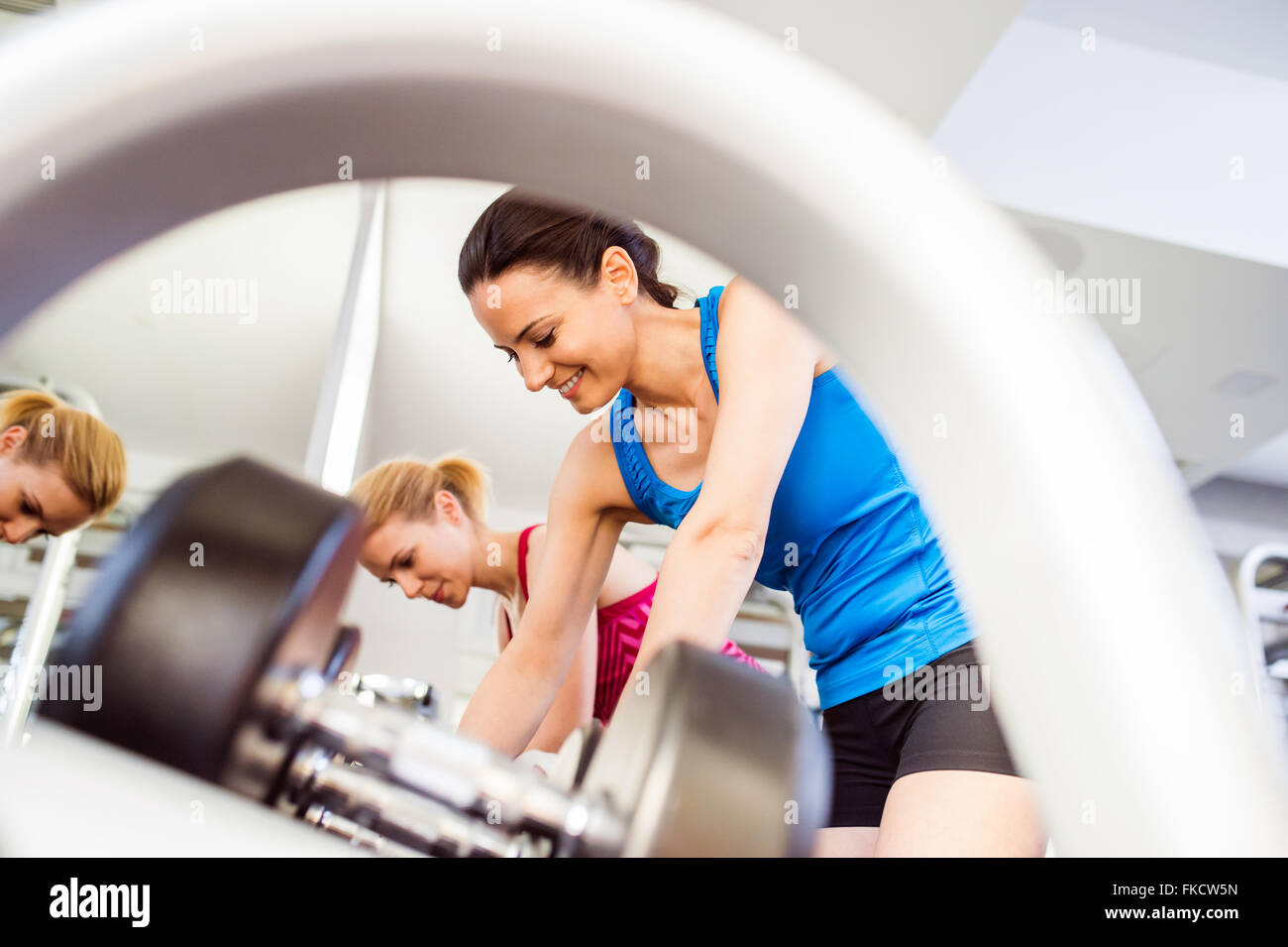 Detail of women in gym working out with weights - Stock Image