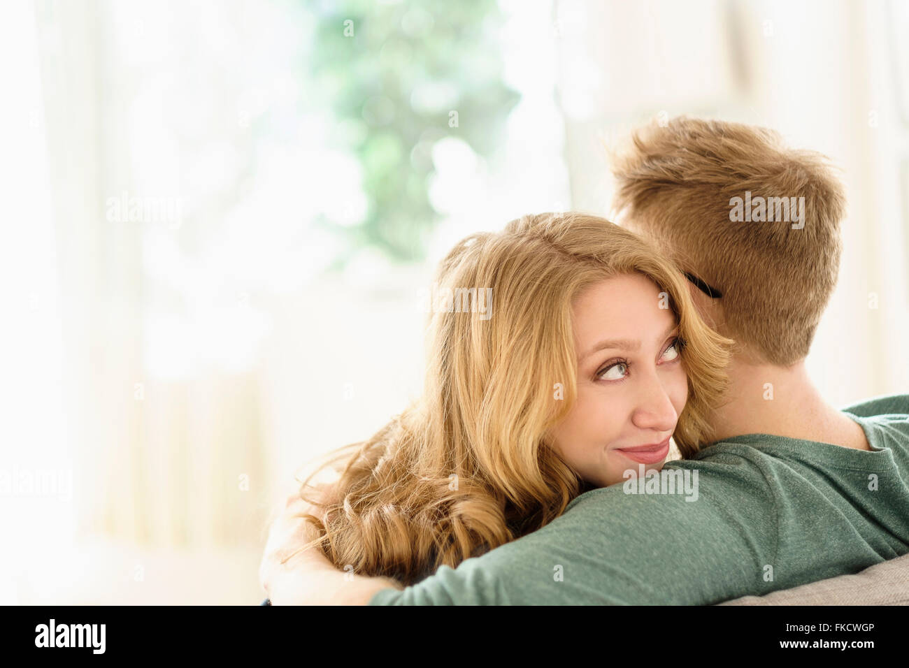 Young woman looking over boyfriend's shoulder - Stock Image