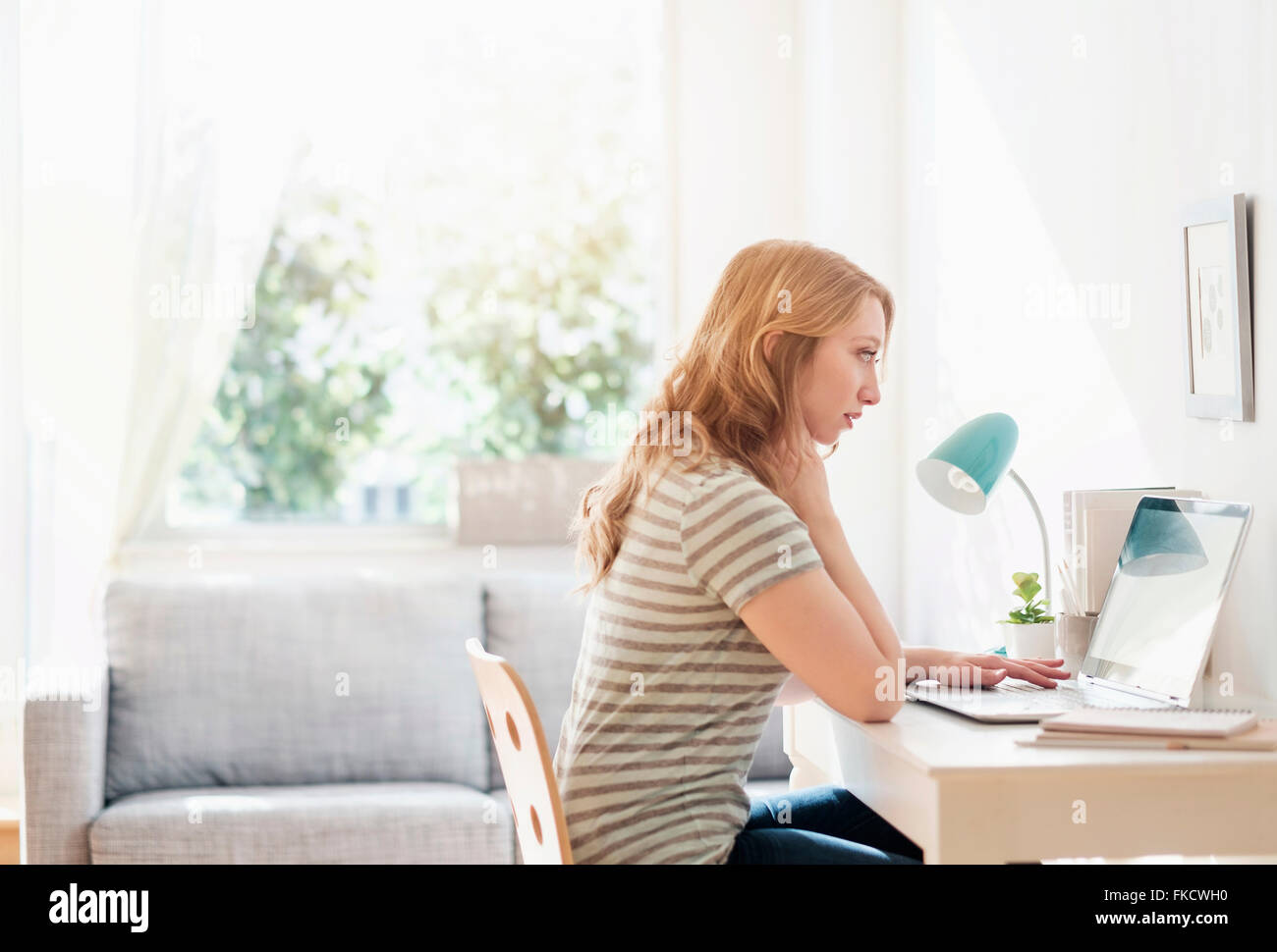Side-view of young woman working on laptop at home - Stock Image
