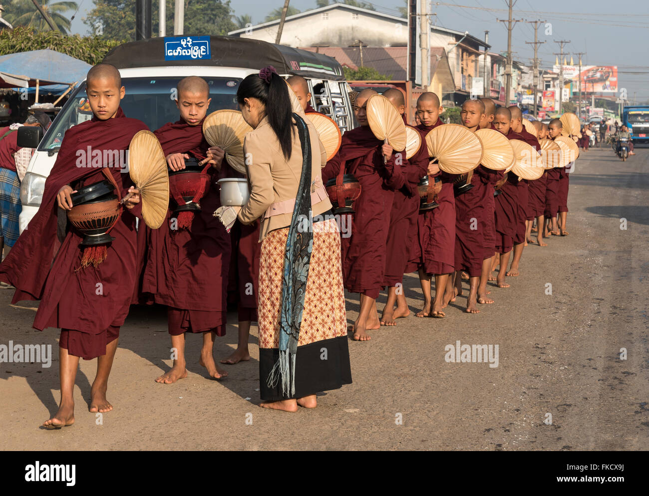 Monks on morning alms round in the streets of Mawlamyaing (Mawlamyine), Burma (Myanmar) Stock Photo