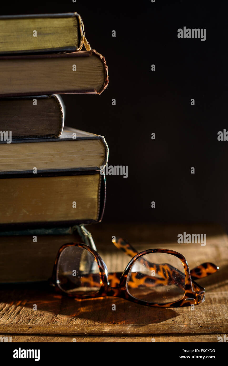 Eyeglasses and stack of books on table - Stock Image