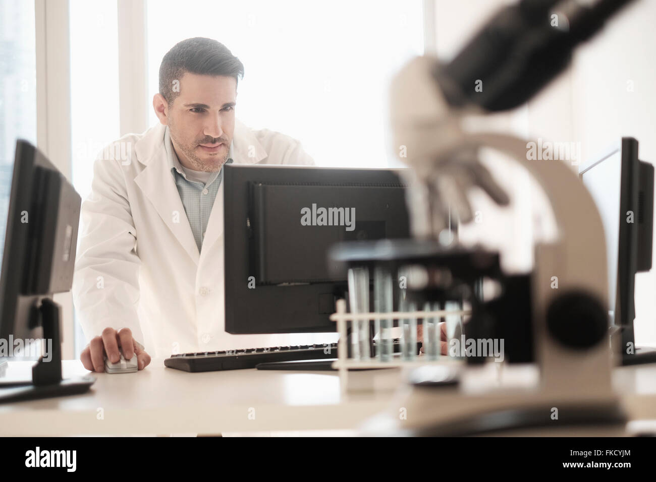 Man using computer in laboratory - Stock Image