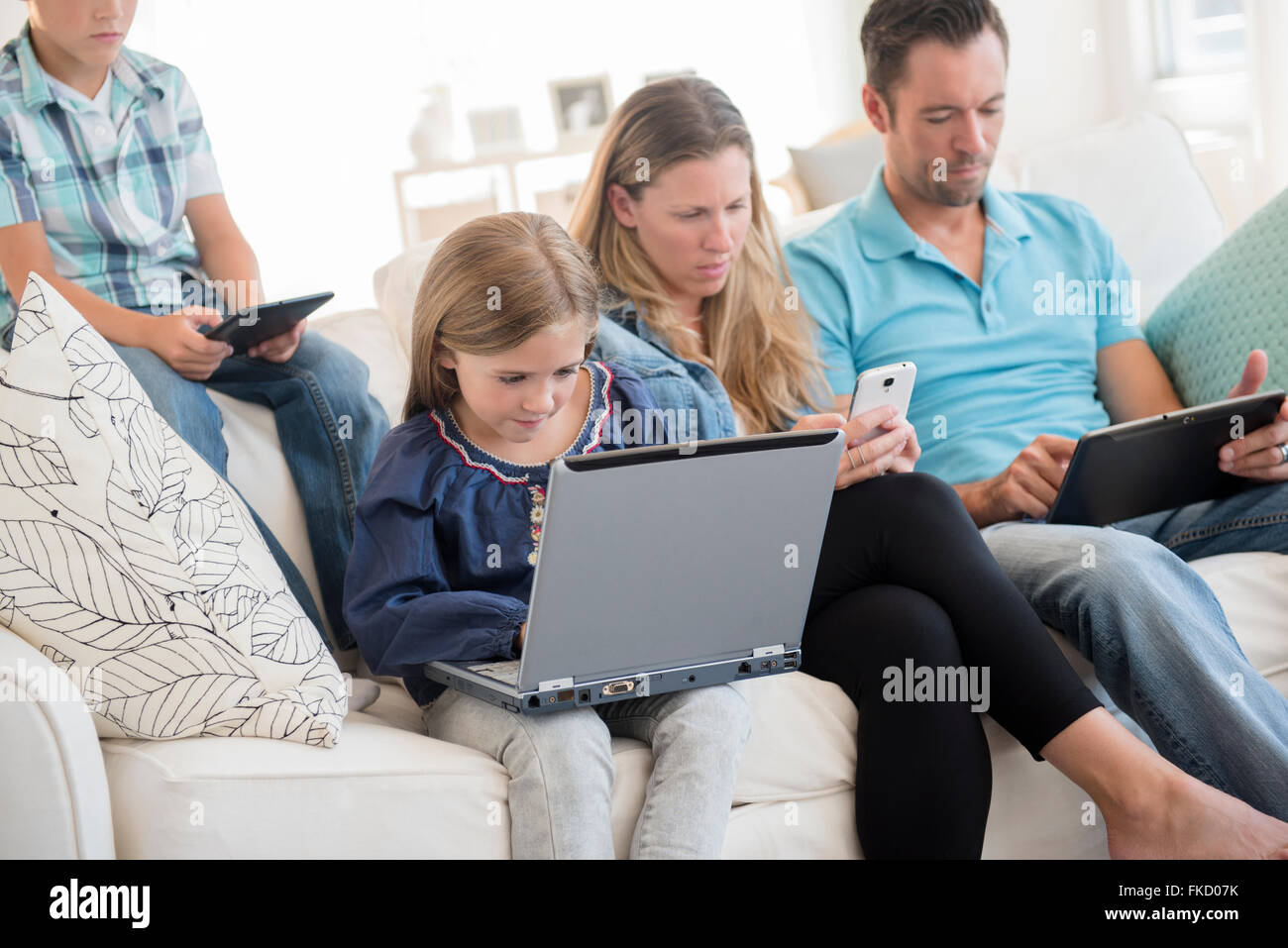Family with two children (6-7, 8-9) sitting on sofa, using laptop and digital tablets Stock Photo
