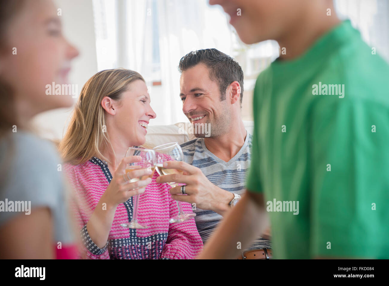 Man and woman sitting on sofa and drinking wine Stock Photo
