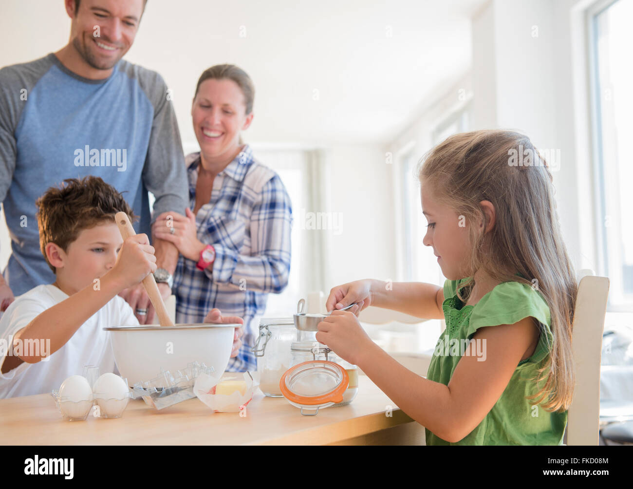 Family with two children (6-7, 8-9) preparing food - Stock Image