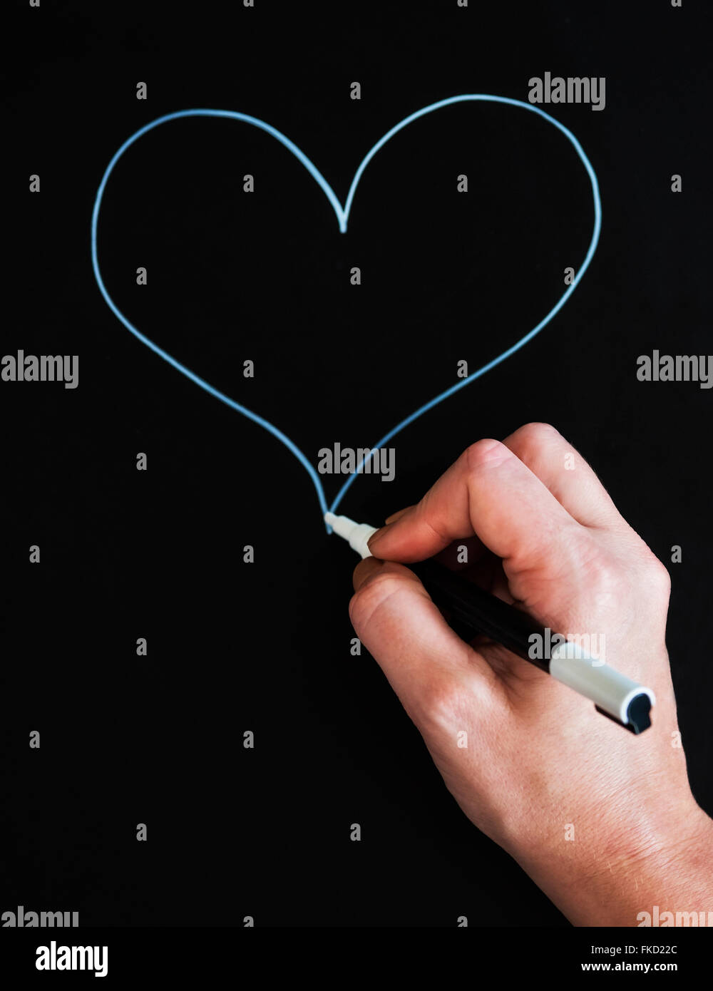 Man's hand drawing heart shape on black paper - Stock Image