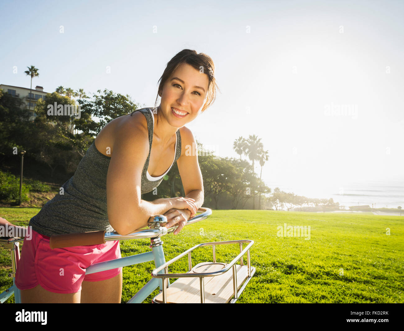 Young woman with bicycle in park Stock Photo