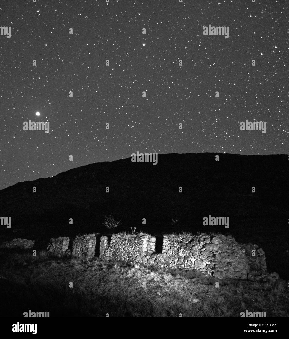 Black and white night time shot of abandoned blackhouse on the Isle of Lewis with a very starry sky - Stock Image