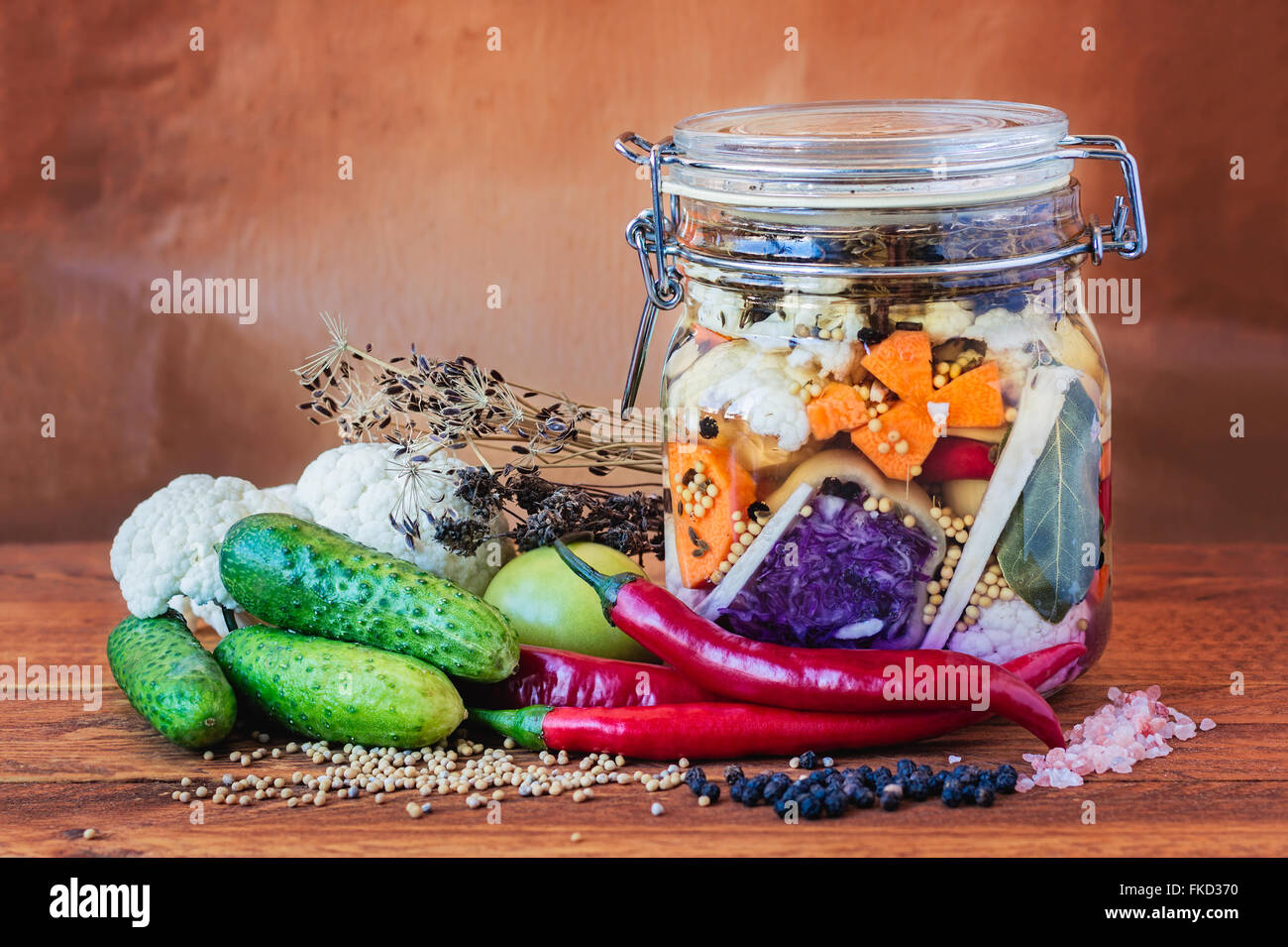Jar of assorted brined lacto-fermented pickles on a wooden table surrounded by vegetables and spices. - Stock Image