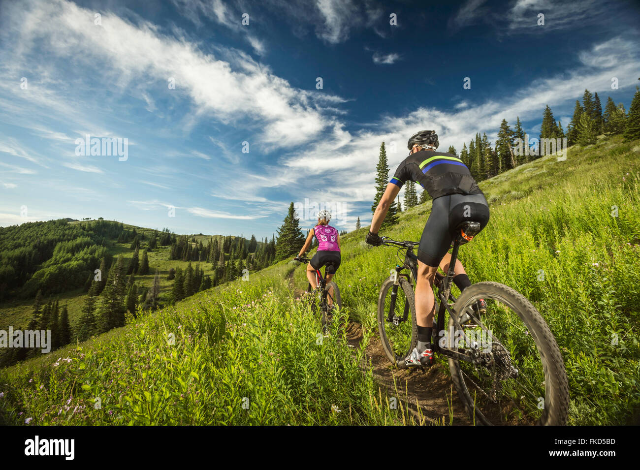 Mature couple during bicycle trip in mountain scenery - Stock Image