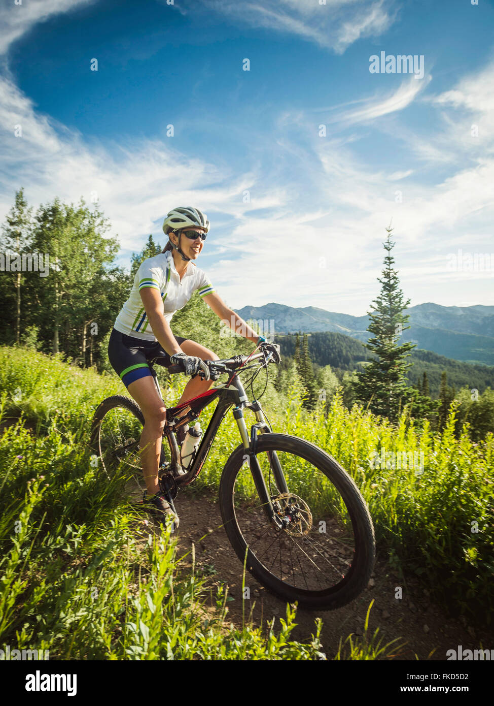 Woman during bicycle trip in mountain scenery - Stock Image