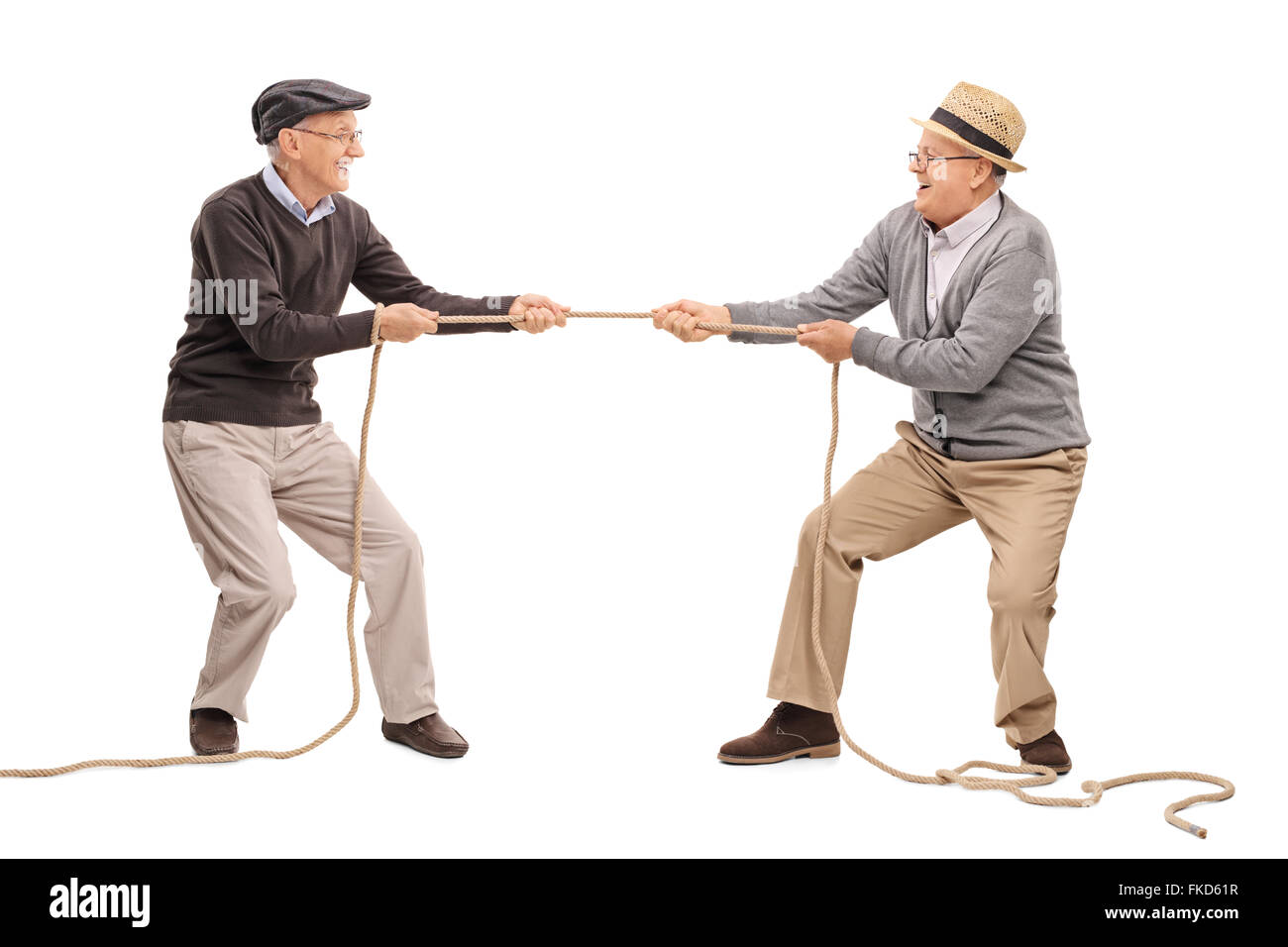 Studio shot of two cheerful seniors competing in a tug of war isolated on white background - Stock Image