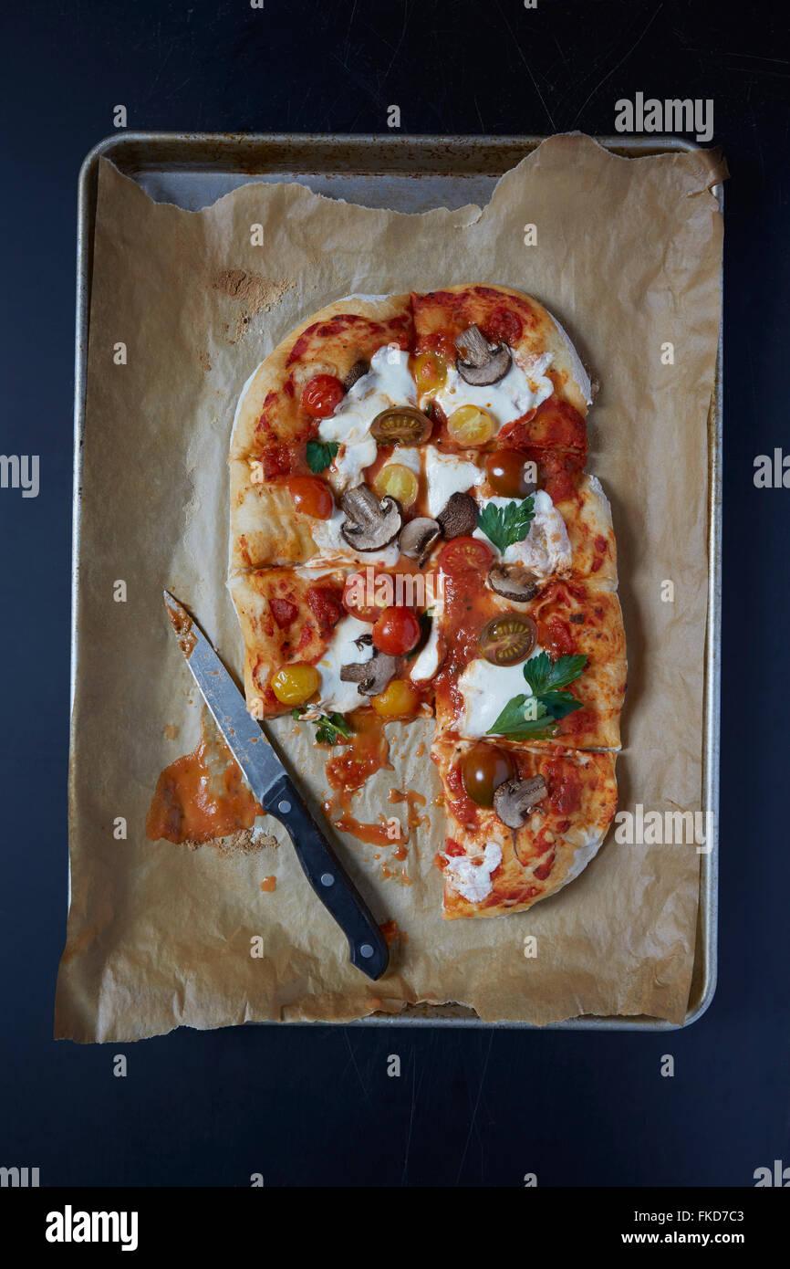 Homemade pizza on baking sheet - Stock Image