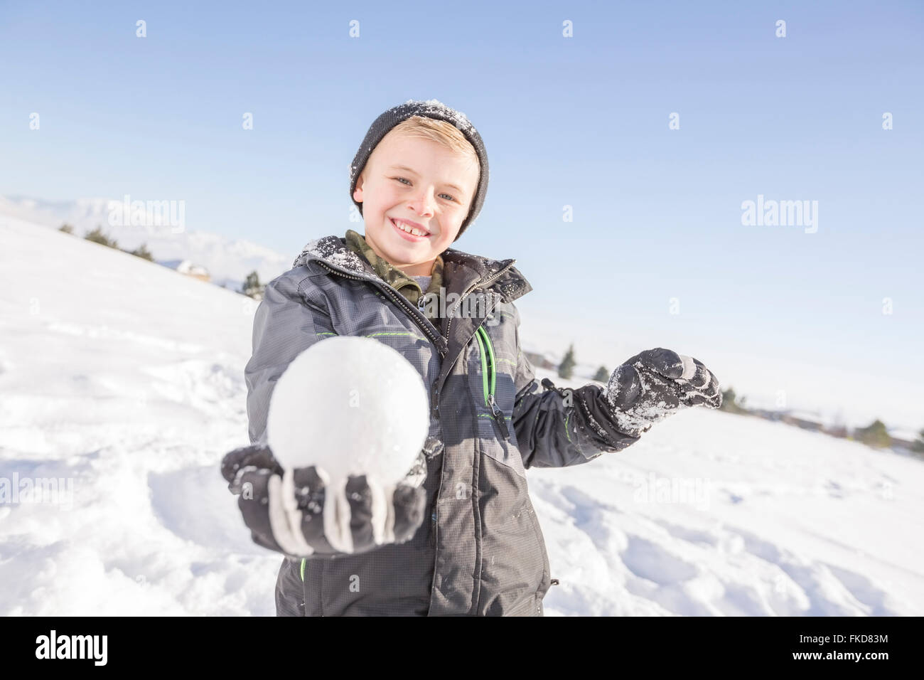 Portrait of boy (8-9) holding snowball - Stock Image
