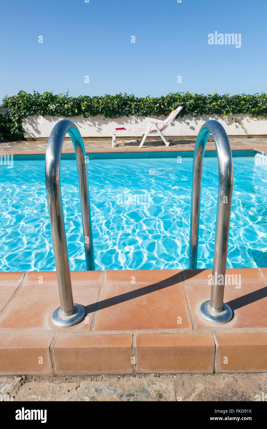entrance to swimming pool with ivy on wall and blue sky and deck chair in the background - Stock Image