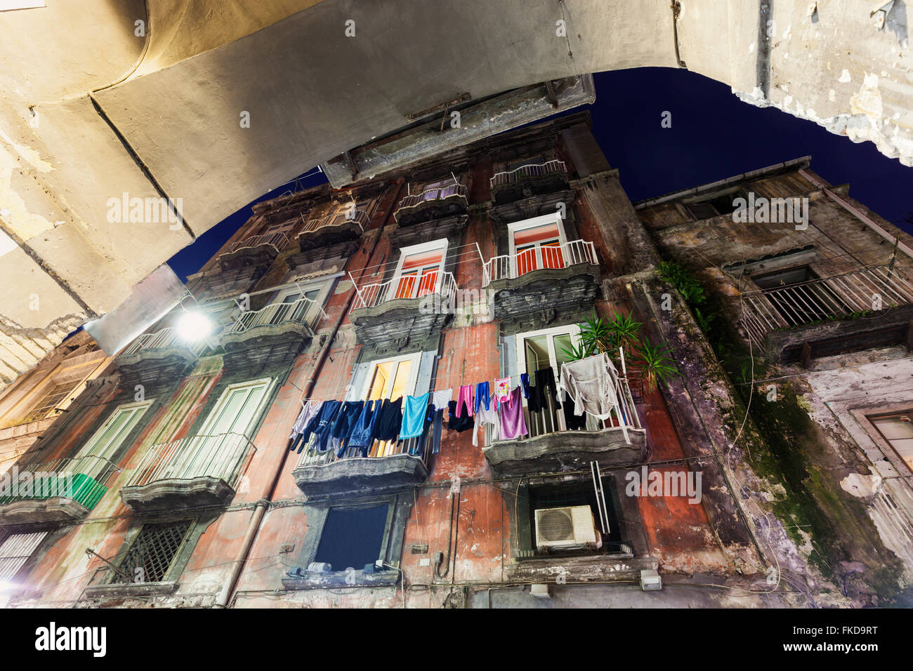 Low angle view of residential building with laundry on balconies - Stock Image