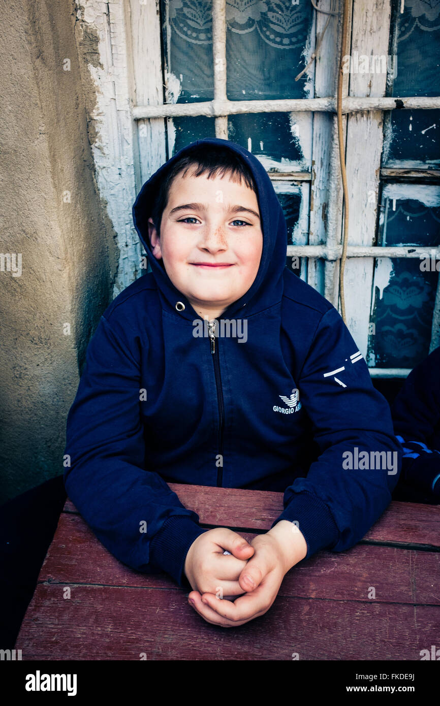 A boy posing for a portrait sat at a wooden table, Tbilisi, Georgia. - Stock Image