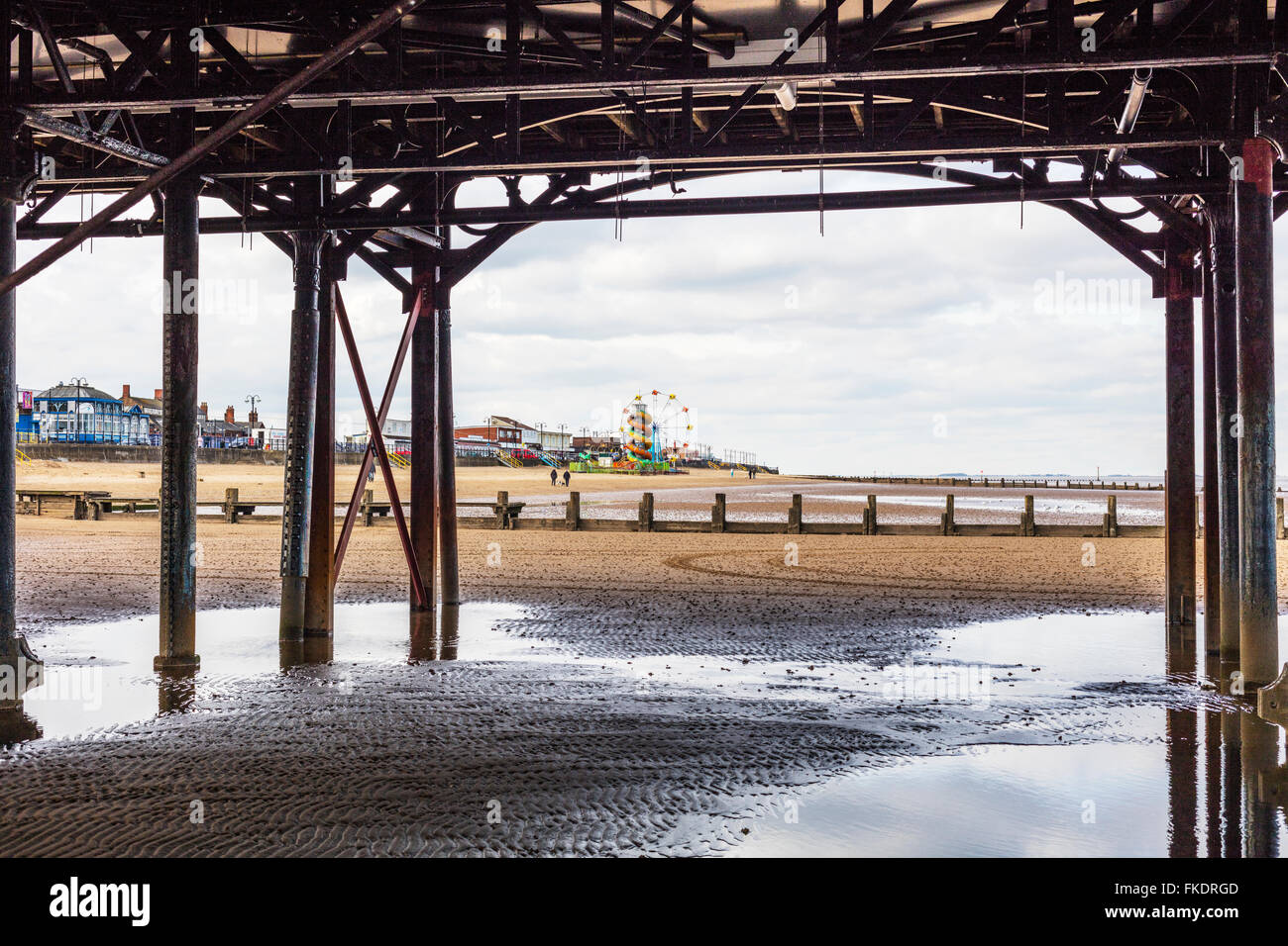Cleethorpes UK beach coastline from under pier towards amusements seafront sea coast coastal town towns England - Stock Image