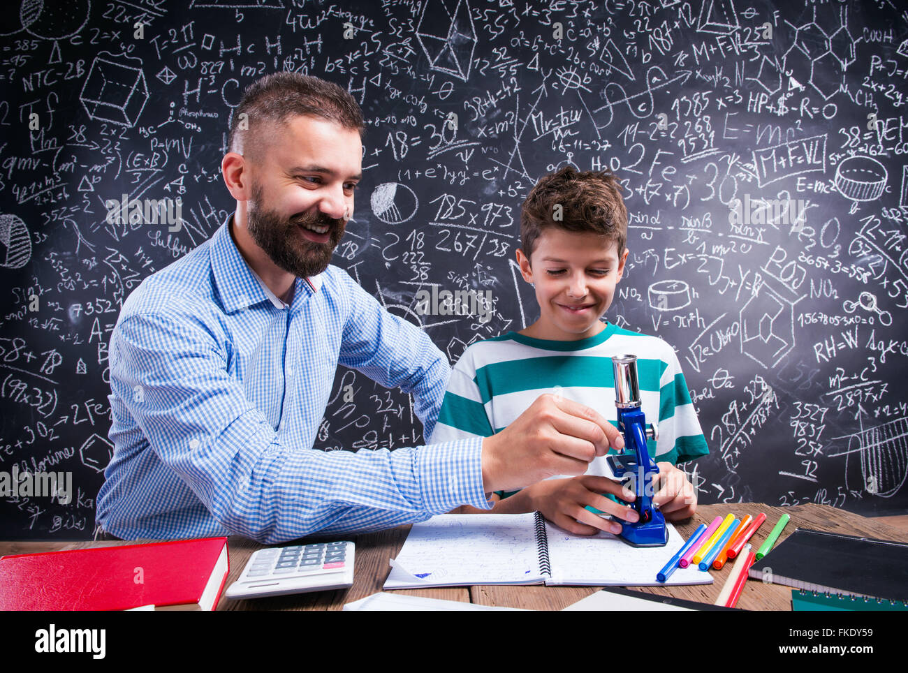 Hipster teacher with his student with microscope, big blackboard - Stock Image