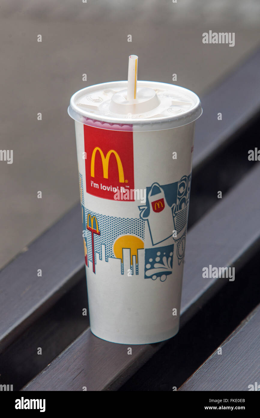 McDonald's Cup with Straw on the bench - Stock Image