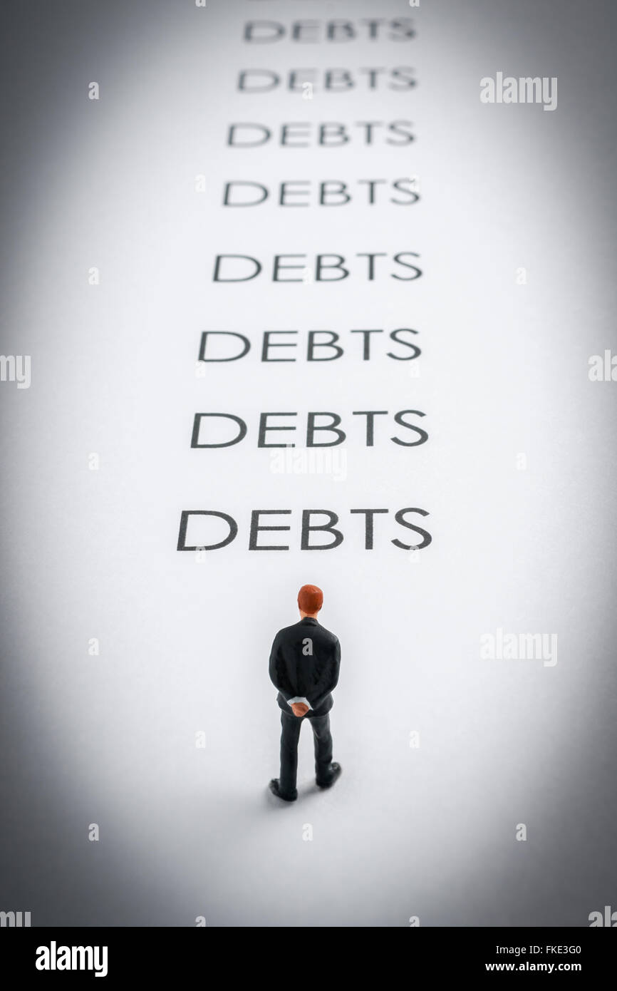 Business man gloomily pondering debt stretching in to the distance a finance or debt concept - Stock Image