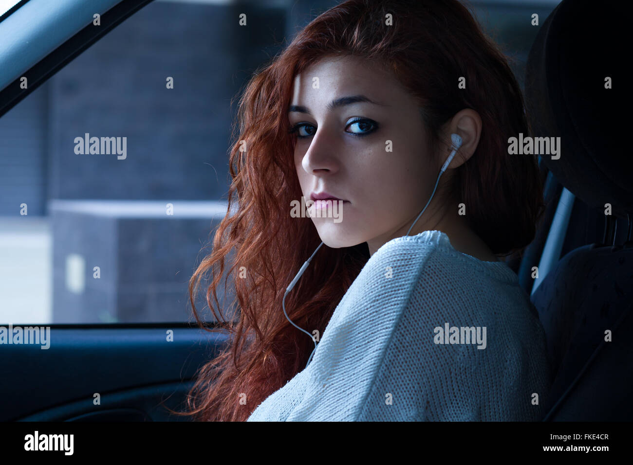 Redhead Woman with Earbuds Sitting in a Car - Stock Image