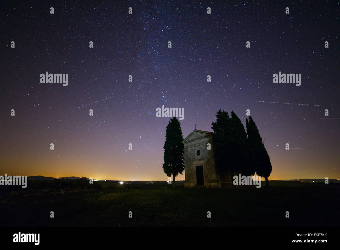 Italy. Tuscany. Lonely chapel and cypress trees in a field. Night sky with myriads of stars - Stock Image