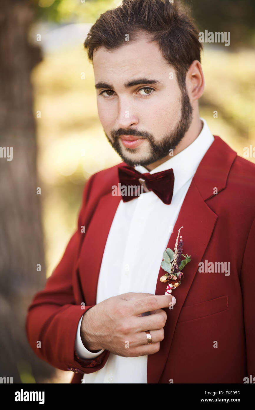 Portrait of groom in red suit with a bow tie, beard and mustache. - Stock Image