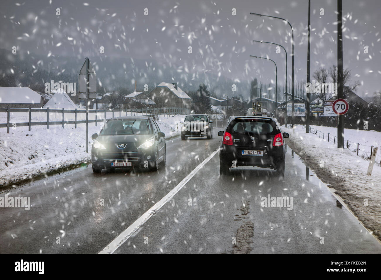 Cars on slippery road during heavy snow shower causing dangerous wintry wet driving conditions in winter / spring - Stock Image