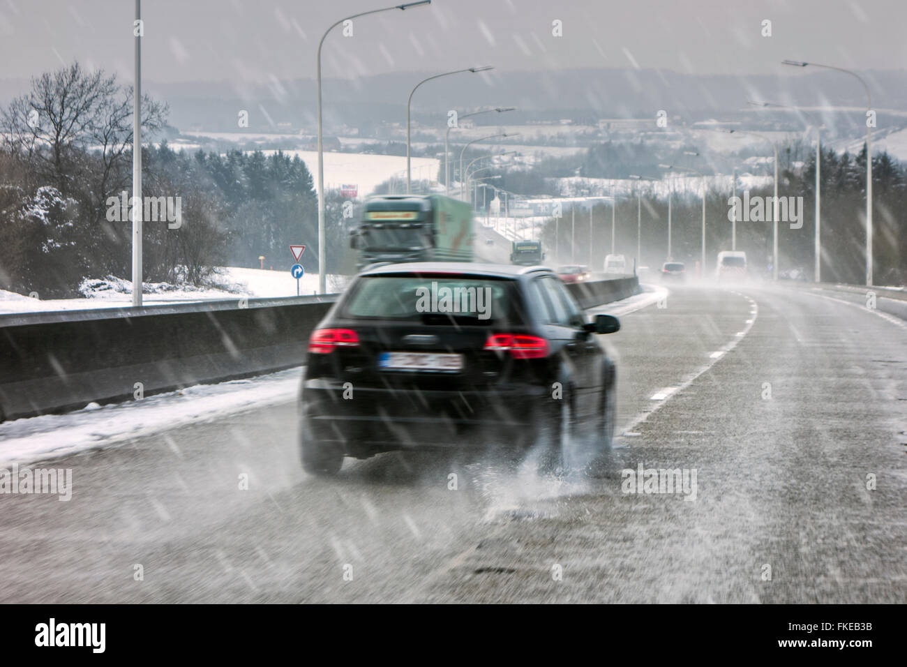 Cars driving on slippery highway during sleet causing dangerous wintry wet road conditions in winter / spring - Stock Image