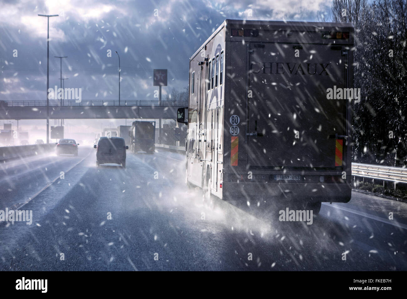 Cars and trucks driving on highway during sleet causing dangerous wintry wet road conditions in winter / spring - Stock Image