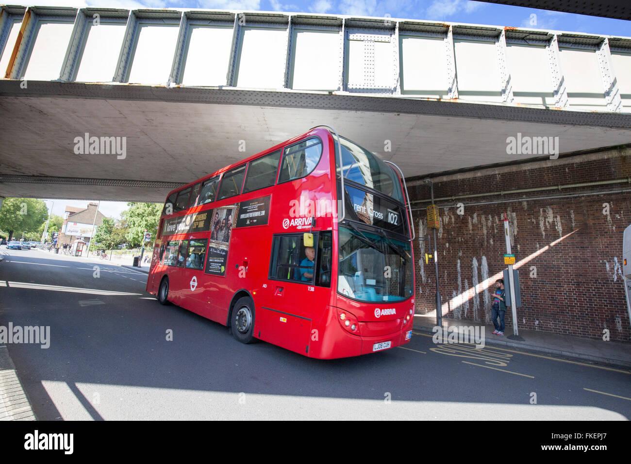 Red Routemaster bus going under railway bridge Stock Photo