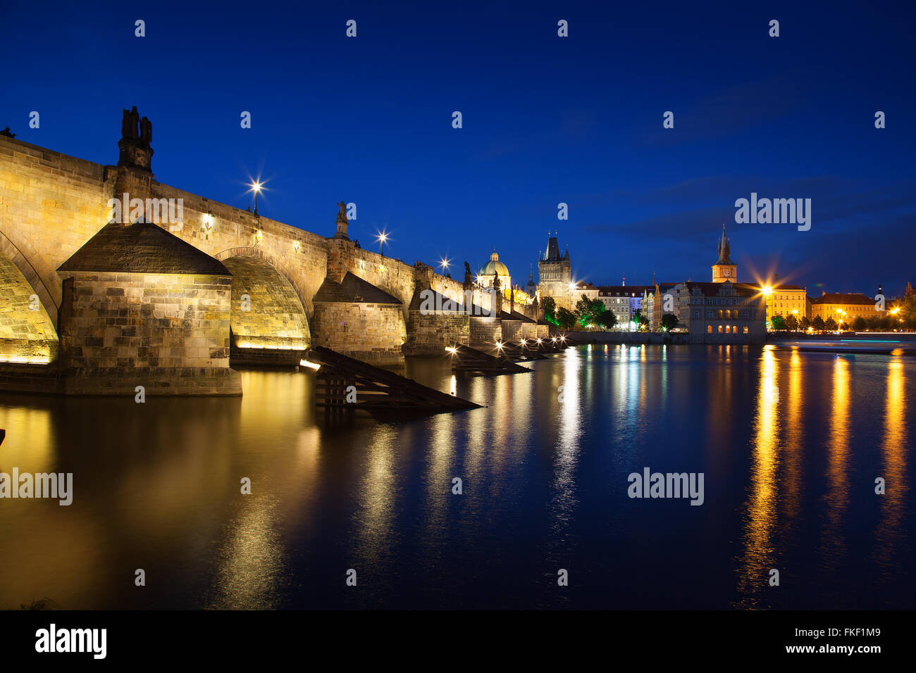 View at night across the Vltava River in Prague with Charles Bridge St Francis Church - Stock Image