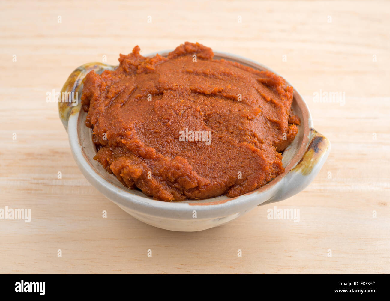 Side view of a small bowl filled with red curry paste on a wood table top. - Stock Image