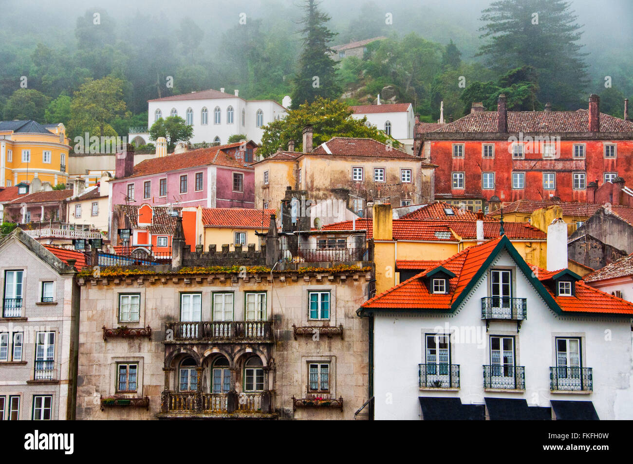 View facades of houses of the city of Sintra in a foggy day - Stock Image