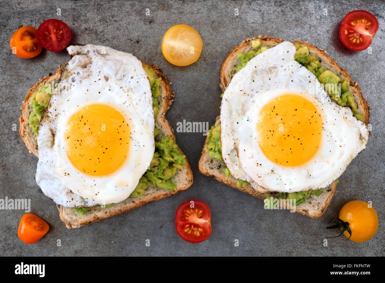 Open avocado, egg sandwiches on whole grain bread with tri-colored tomatoes on rustic baking tray Stock Photo
