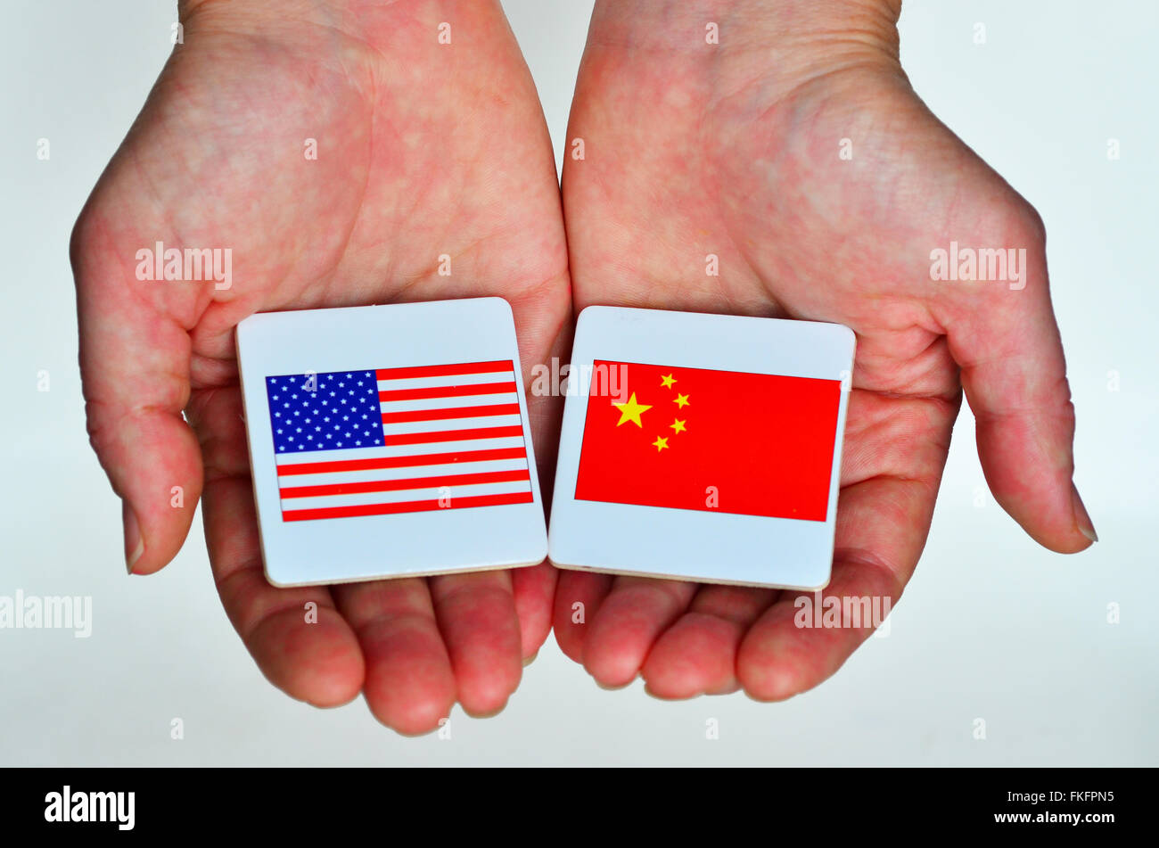 Two hands holds the national flags of the United States of America (L) and of the Republic People of China (R) beside - Stock Image