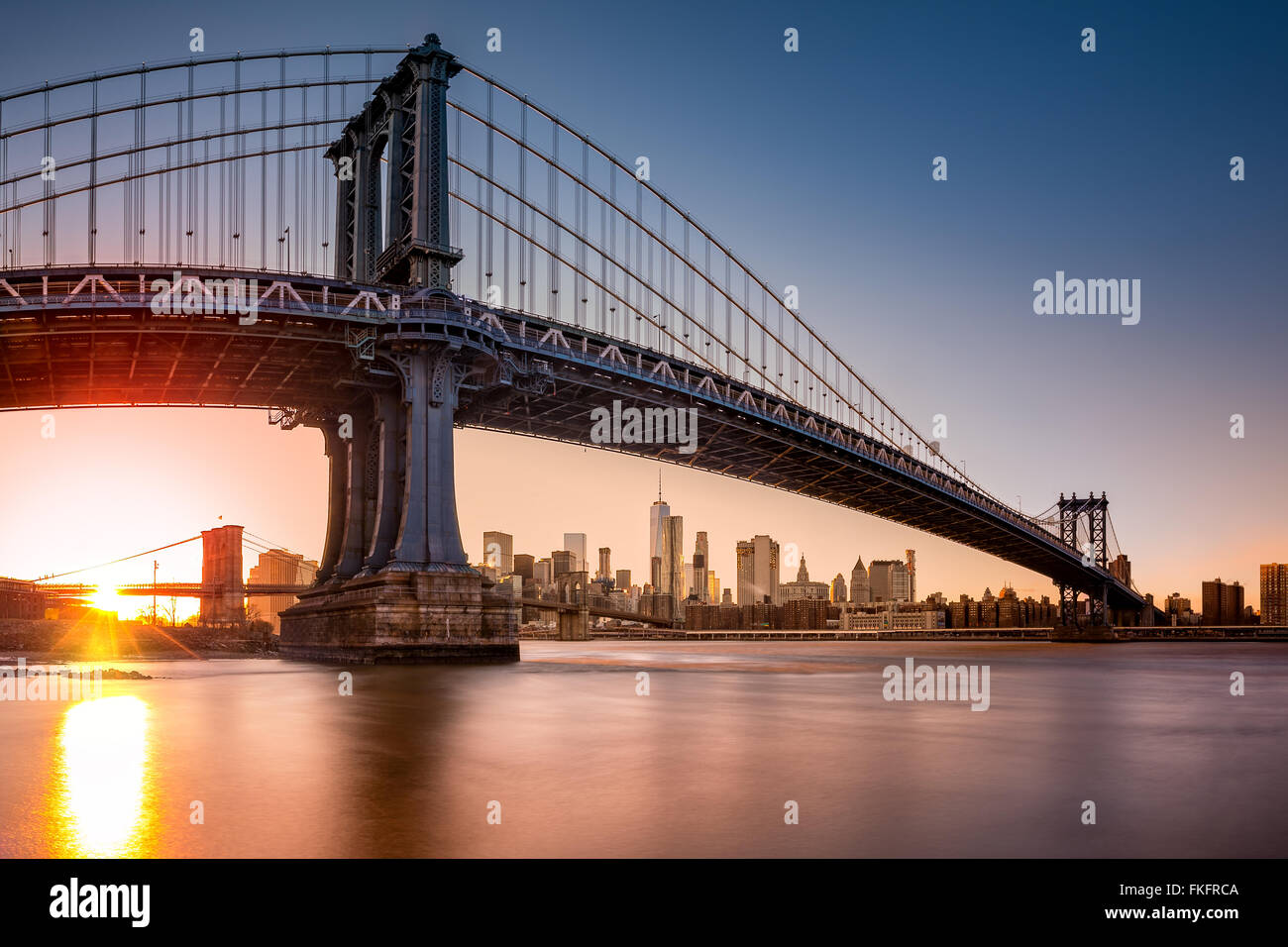 Manhattan Bridge framing New York skyline at sunset. - Stock Image