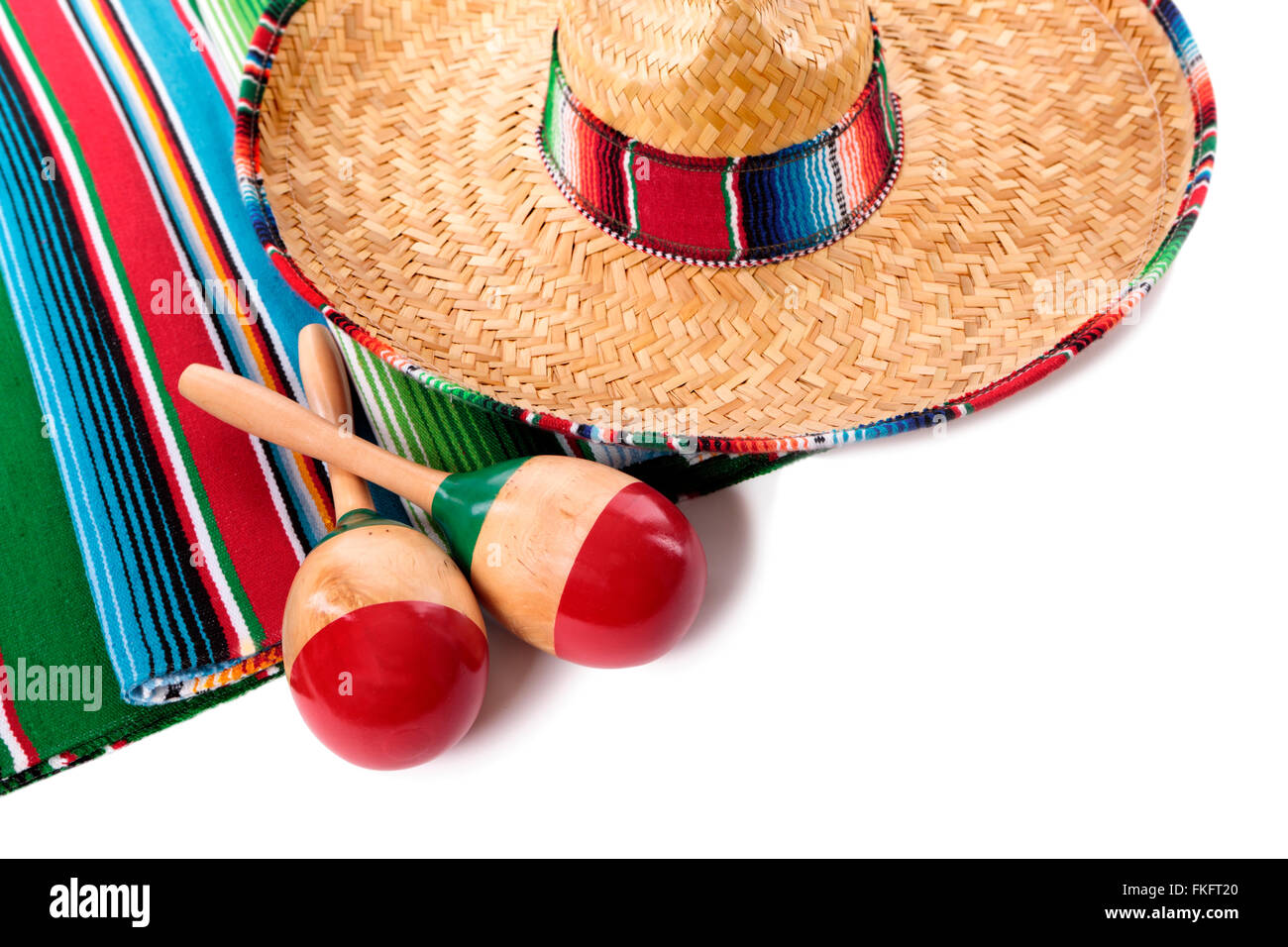 Traditional Mexican serape blanket or rug with sombrero and maracas isolated against a white background.  Space Stock Photo