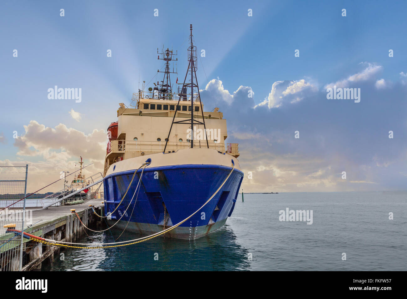 Moored nautical vessel at a pier with sun rays shining behind - Stock Image