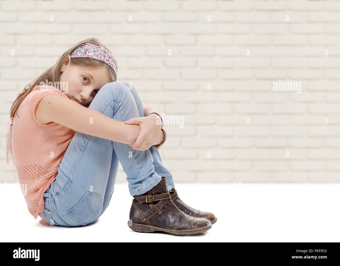 a pre-teen girl sad n is sitting on the floor - Stock Image