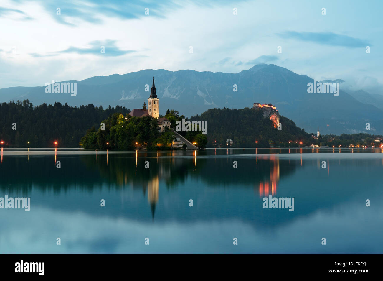 Lake bled with the illuminated St. Mary´s Church of the Assumptionon at dusk. - Stock Image
