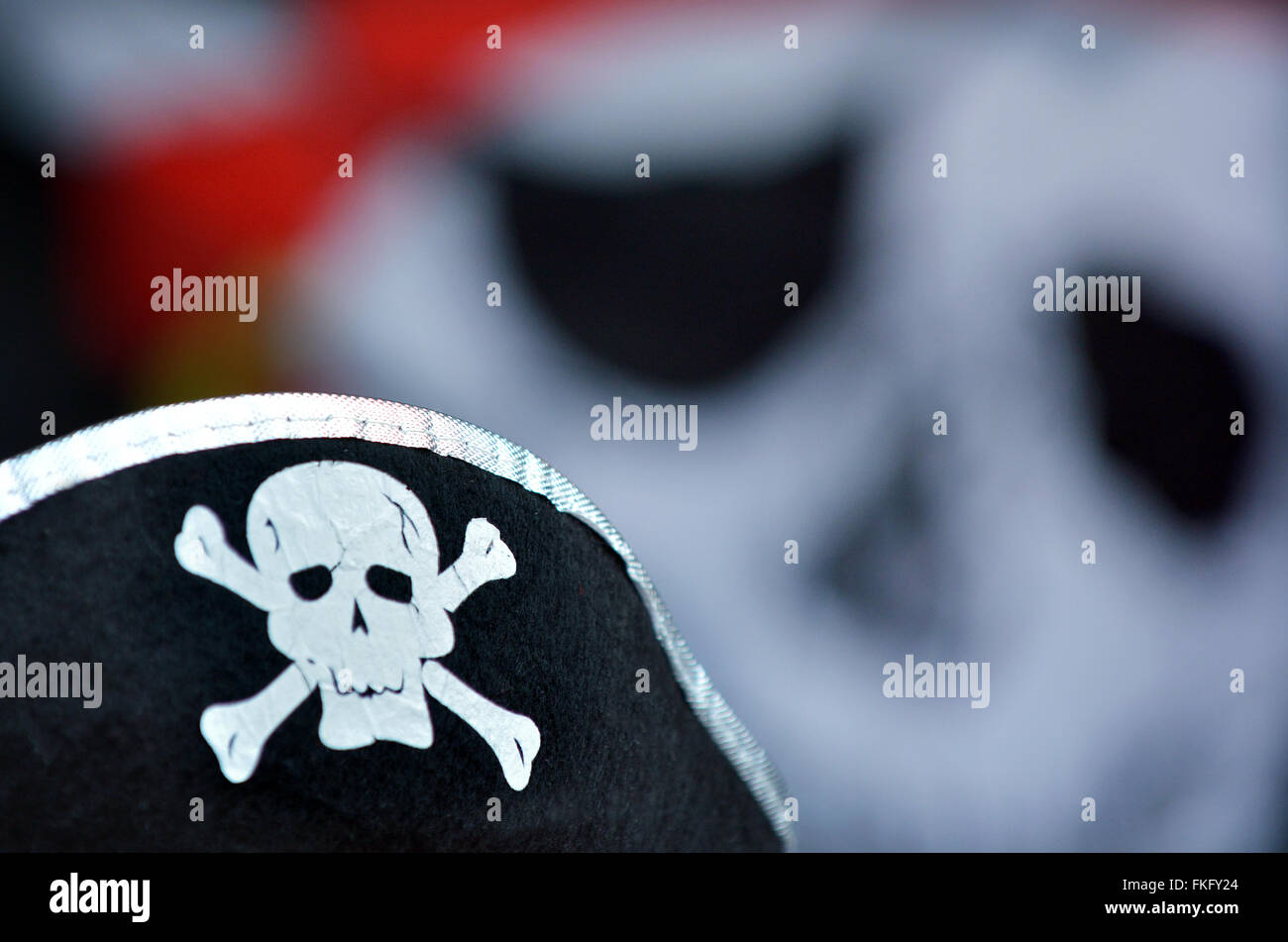 Pirate hat with skull and bones sign and Jolly Roger flag in the background. - Stock Image