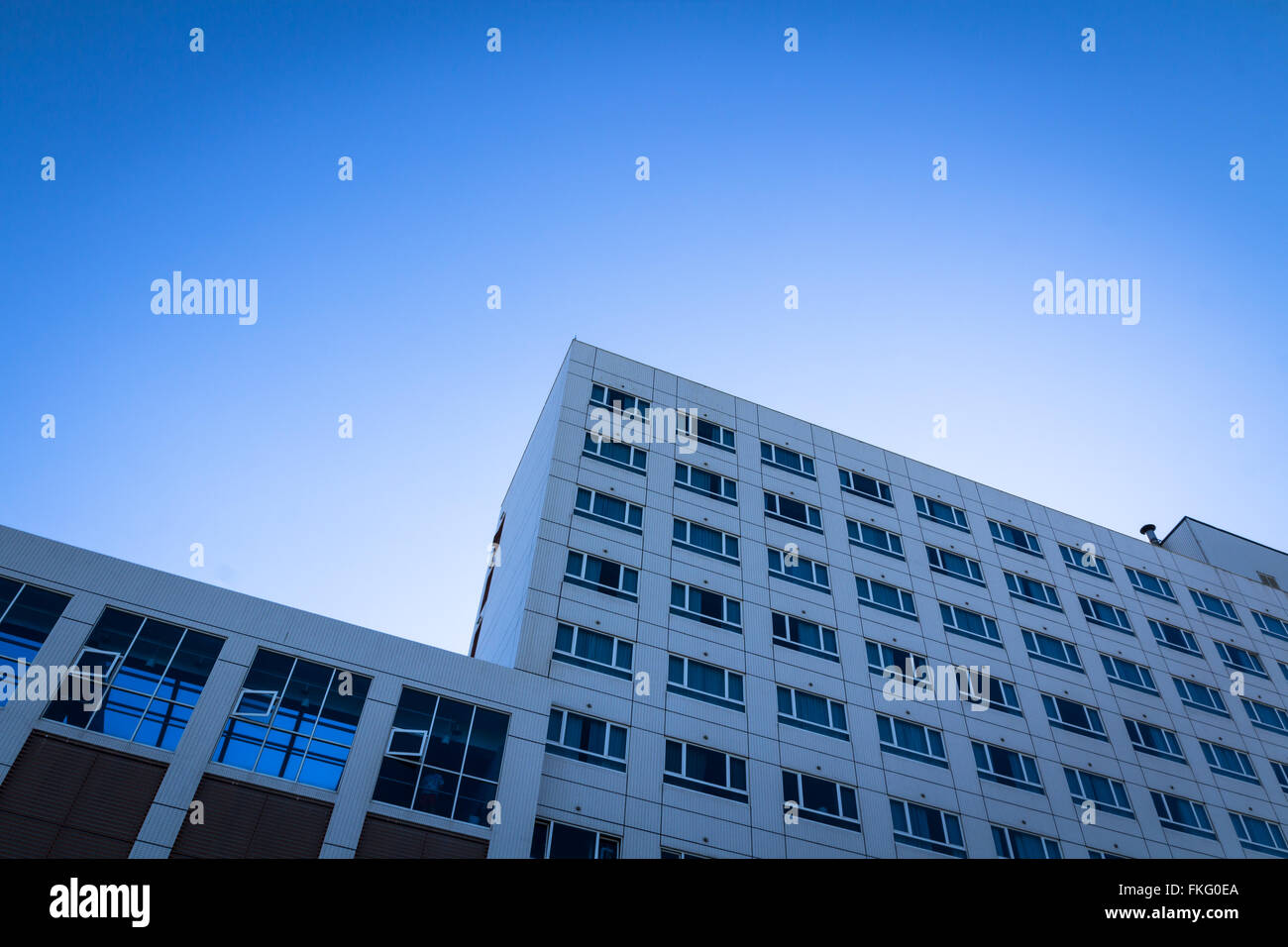 square side of pane in business center over blue bright sky. - Stock Image