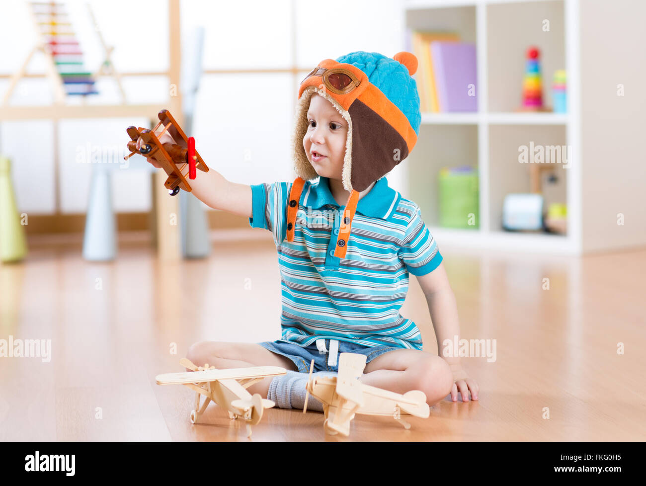 happy child toddler playing with toy airplane and dreaming of becoming a pilot Stock Photo