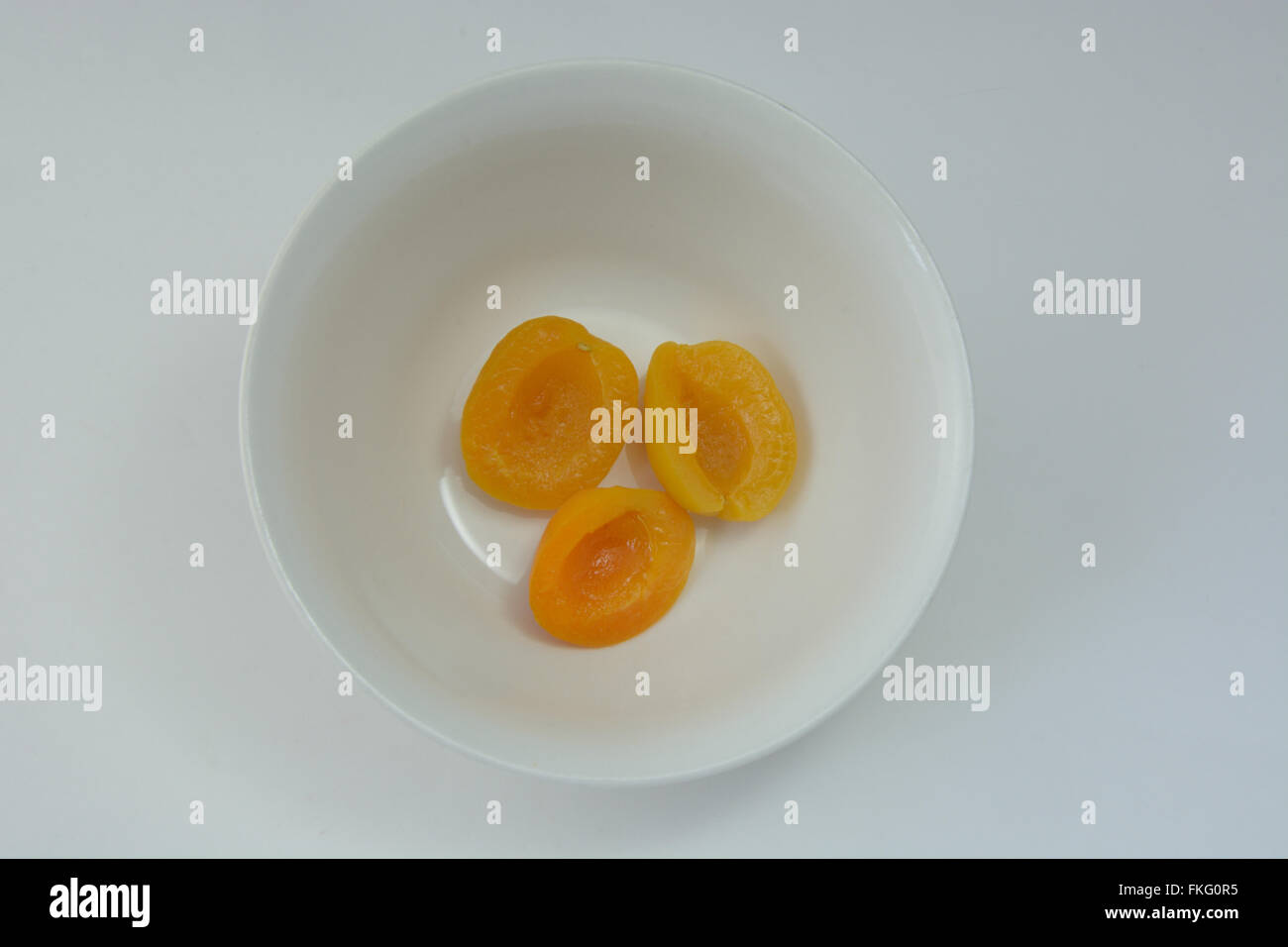 Canned apricot halves in white bowl - Stock Image