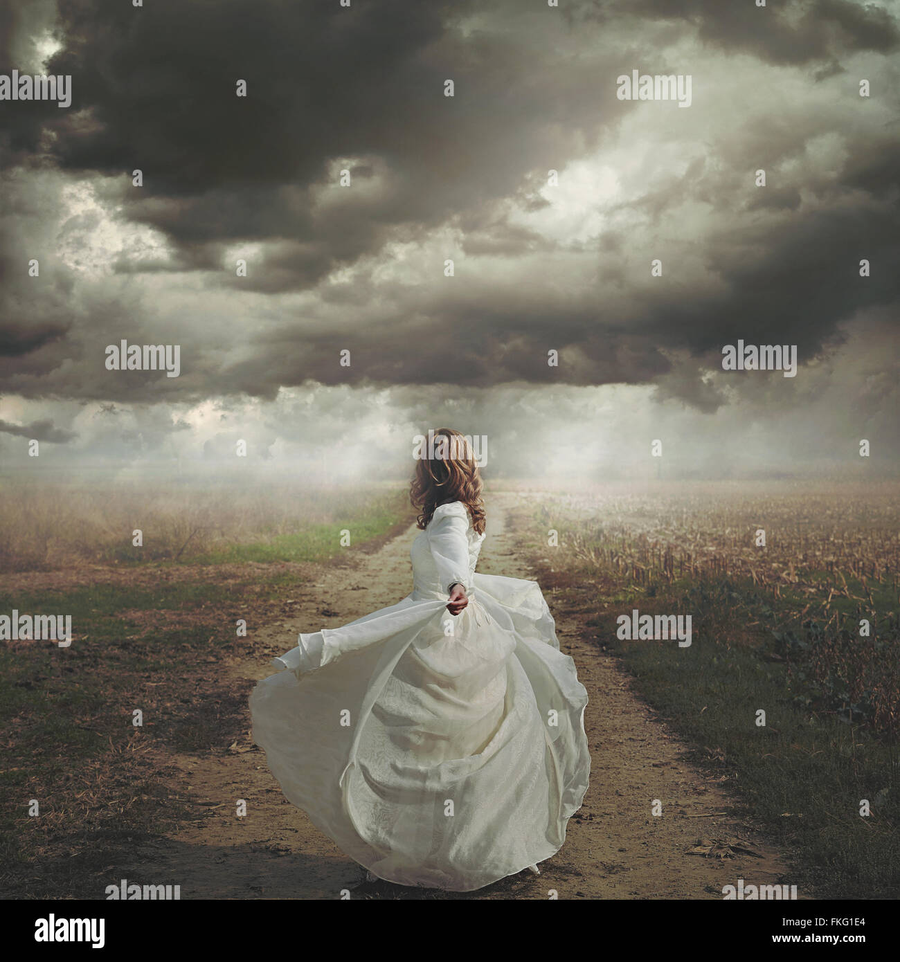 Woman dancing in desolate road. Dramatic and surreal cloudscape - Stock Image